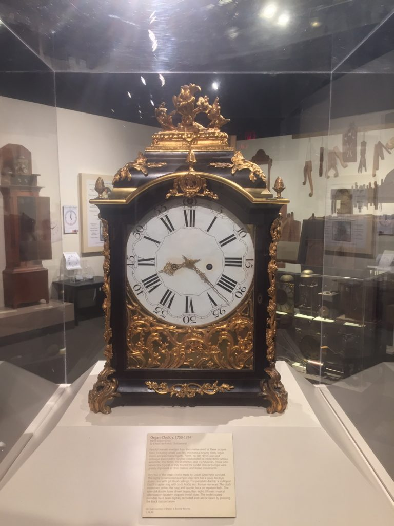 big golden clock behind glass case